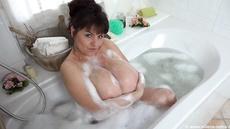 Женщина моет в ванне огромные зрелые сиськи